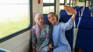 Two young muslim woman in hijab, taking selfie with phone.