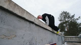Urban city parkour - athlete tracer performs free-running in winter park