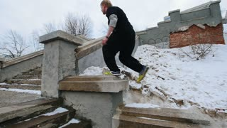 Urban city parkour - slow motion acrobatics - steadicam shot of a young athlete performing jumping in winter park