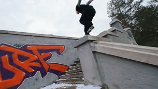 Urban city parkour - slow motion jumping - athlete performing free-running in winter park