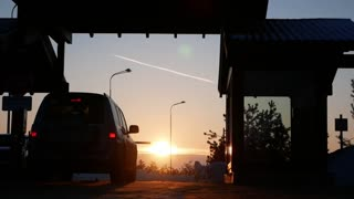 Vehicles driving to barrier of check-point - pay road at sunset, silhouette