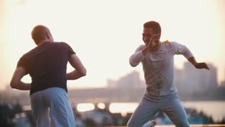 Very strong men show skills of dance of capoeira, fight on a grass, smile, at a sunset