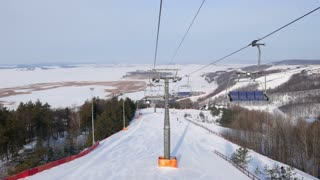 View from cabin of cable car on sky resort at sunny winter day
