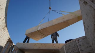 View from inside house - working construction crane lifts the straw wooden block for circle ecology house