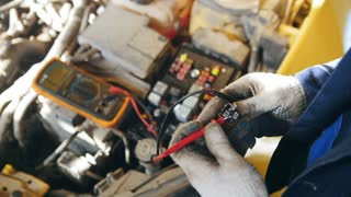 Voltmeter in the car - automotive electrician checks electro relay in the car, small business - auto garage service