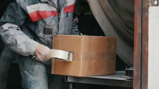 Warehouse workers packing up box in a industrial warehouse