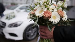 Wedding bouquet in front of luxury car
