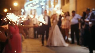 Wedding fireworks - sparkler in hands on a wedding - bride, groom and guests holding lights in, de-focused and slow-motion