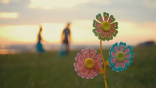 Wind-up toy, family fun background, bright green grass, orange sunset