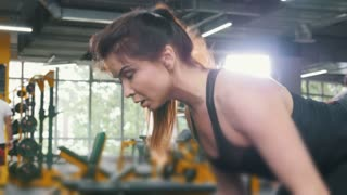 Woman athlete lifting dumbbells in the gym - close up