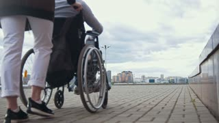 Woman carries a disabled man in a wheelchair walking down the street