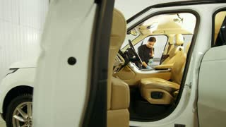 Woman in blue gloves is cleaning interior of the car for luxury SUV