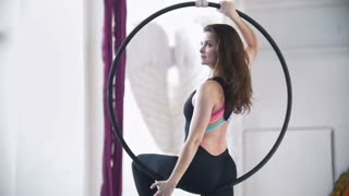 Woman makes a gymnastic elements on the aerial hoop