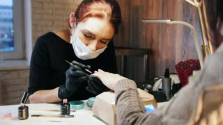 Woman manicurist in medical mask doing manicure in beauty salon
