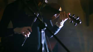 Woman playing the violin at rock concert