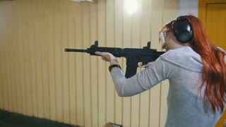 Woman shooting with a Mashin gun in shooting gallery
