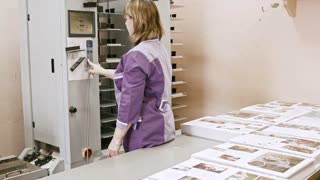 Woman working on folder machine in printing house - polygraph industry