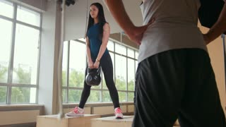 Woman working out doing squats with weigh in the gym