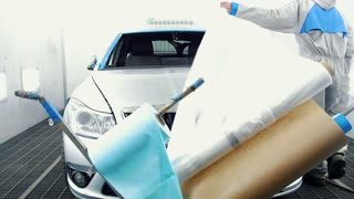 Worker covers the car before painting - professional car painter in vehicle workshop