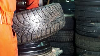 Worker in car service repairs tires - mechanical workshop