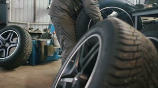 Worker in car service repairs tires - mechanical workshop