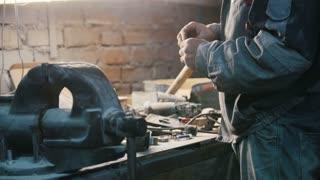 Worker in dusty vintage workshop - making repair, close up