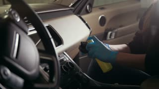 Worker in gloves is puting cream on the brush and washing a car interior