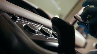Worker in gloves is washing with brush a car dashboard and button