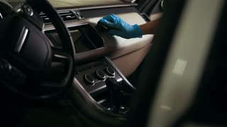 Worker in gloves is washing with brush a car dashboard