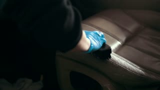 Worker in gloves is washing with brush a car seats