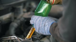 Worker in gloves pouring new motor oil at the service station