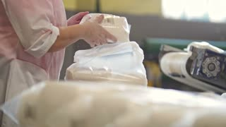 Worker packing bags with crystal sugar at the sugar factory