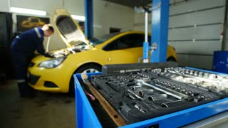 Worker works in professional car workshop near yellow car, time-lapse