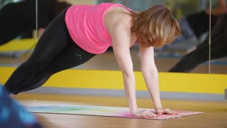 Yoga in the gym - coach shows fitness exercise for mature women