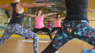 Yoga in the gym - coach shows fitness exercise for women