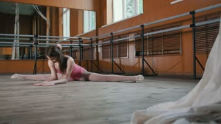 Young athletic acrobatic girl sits on a splits