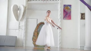 Young attractive ballerina in white tutu performs pirouette in spacious studio