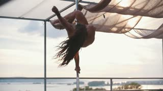 Young attractive girl with flowing hair dancing outdoor - pole dance