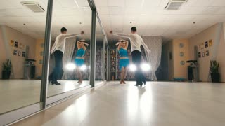 Young attractive man and woman dancing and rehearsing Latin dance in costumes in the Studio