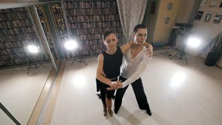 Young attractive man and woman dancing Latin American dance in costumes in the Studio, top view, slow motion