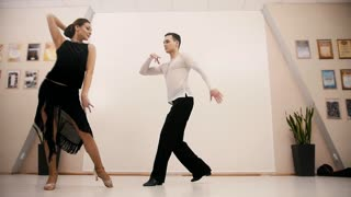 Young attractive man and woman dancing Latin dance in costumes in the Studio, slow motion