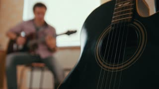 Young attractive man musician composes music on the guitar and plays, other musical instrument in the foreground, blurred concept