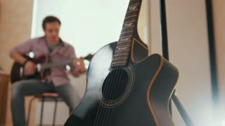 Young attractive musician composes music on the guitar and plays, other musical instrument in the foreground, blurred concept