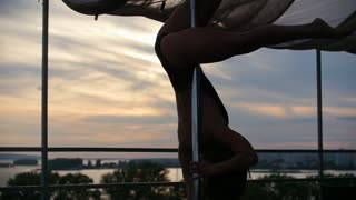 Young beautiful girl dancer with flowing hair dancing outdoor - pole dance near mirror