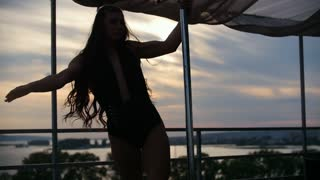 Young beautiful girl dancer with flowing hair dancing outdoor - pole dance, silhouette slow-motion