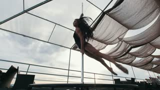 Young beautiful girl dancer with flowing hair rotated around pole - dance outdoor, slow-motion