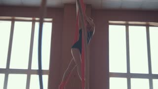 Young beautiful girl in the splits hanging on the hoop
