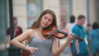 Young black hair woman playing a violin at the pedestrian street