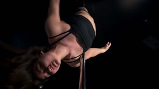 Young brunette dancing with a pole in a studio