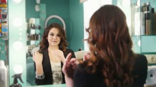 Young brunette in a beauty salon admiring her reflection in the mirror